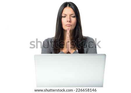 Young student or business woman with a stern expression and hands clasped in hope or prayer sitting at her desk behind a laptop computer - stock photo