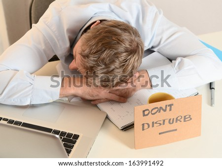 Young Student or Businessman Overwhelmed sleeping with Dont Disturb sign written on cardboard - stock photo