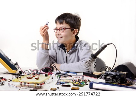 Young student performs experiments in electronics and dreams of the future. - stock photo
