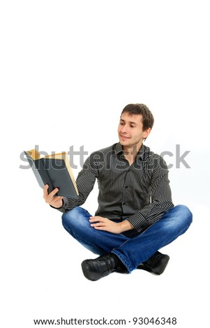 Young student reading a book sitting on the floor - isolated on white background