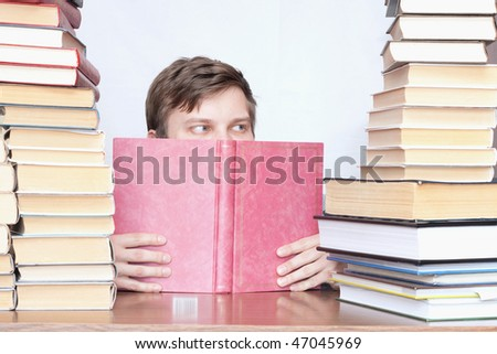 Young student reading book and see sideways between books - stock photo