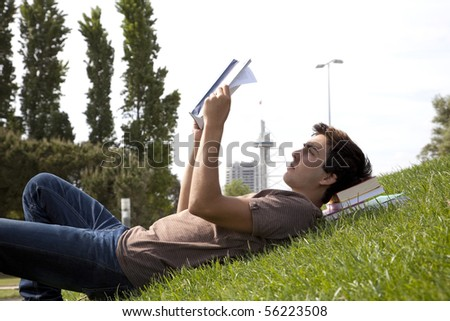 young student reading books at the school park - stock photo