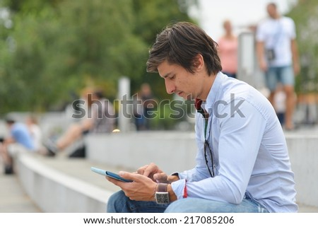 Young student reading on tablet computer in the city
