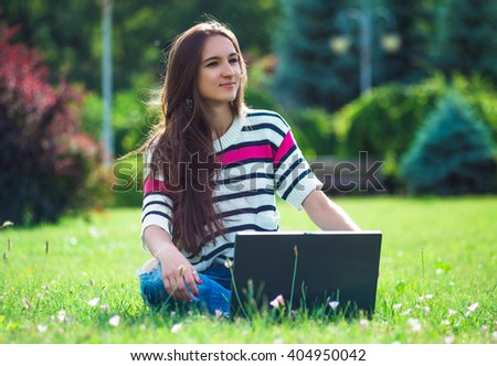 Young student relax in city park. Work with laptop in green grass