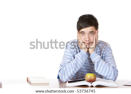 Young student sitting on desk and learns for his exams. He looks sad and tired into camera. Isolated on white. - stock photo