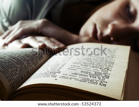 Young student sleeping on table near book
