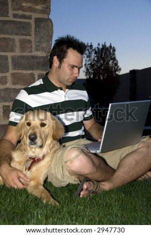 Young student studying with his notebook computer and Golden Retriever dog - stock photo