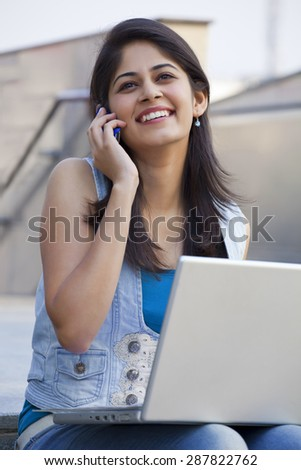 Young student talking on mobile phone in college campus - stock photo