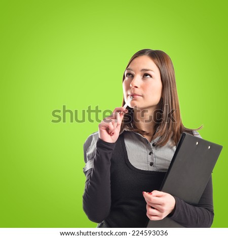 Young student thinking over isolated green background  - stock photo