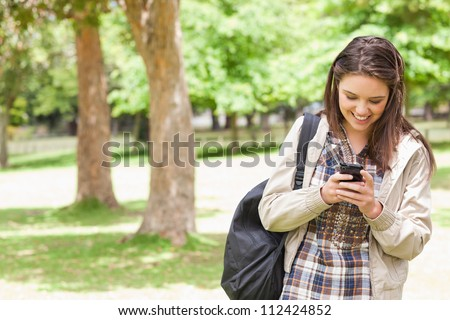 Young student using a smartphone in a park - stock photo
