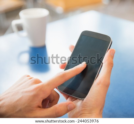 Young student using his smartphone in cafe at the university - stock photo