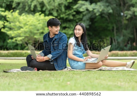 Young student using laptop together in the park - stock photo