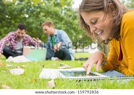Young student using tablet PC while two males using laptop in background at the park - stock photo