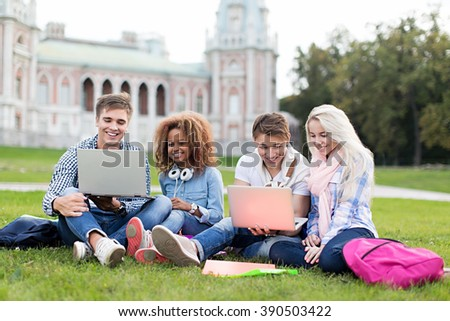 Young student with laptop outdoors - stock photo