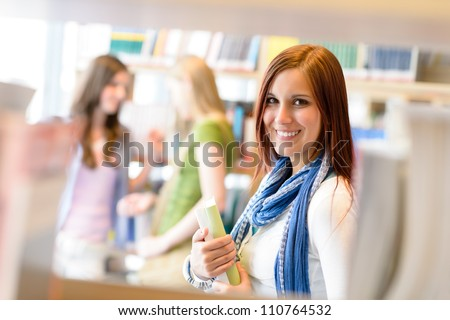 Young student woman choosing book among library shelves - stock photo