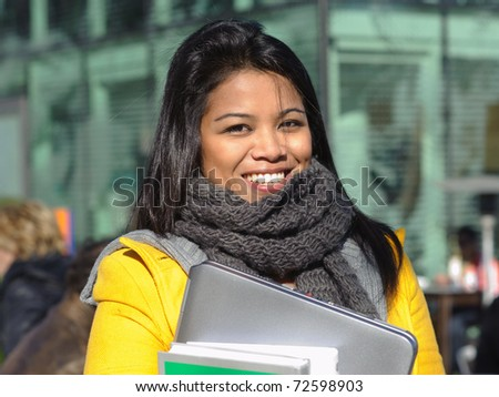 Young student woman holding books and laptop and smiling at camera - stock photo