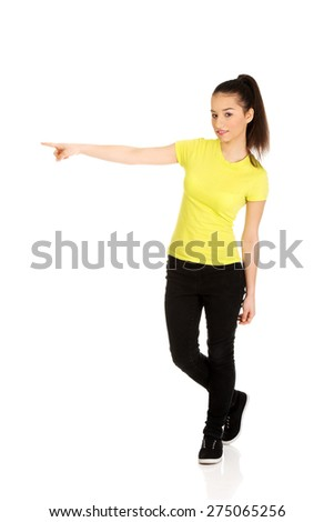 Young student woman pointing aside. - stock photo