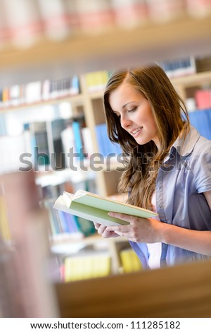 Young student woman reading book among library shelves - stock photo