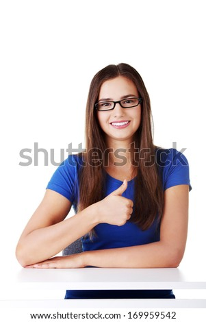 Young student woman showing OK gesture. Isolated on white.
