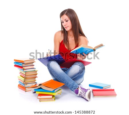 Young student woman sitting on the floor surrounded with books, taking notes, preparing for exam. White background.