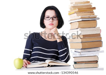 Young student woman with books studying at the desk, isolated on white background