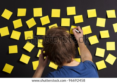 Young student writing a message on a yellow note