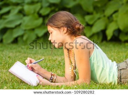 Young student writing into her notebook - stock photo