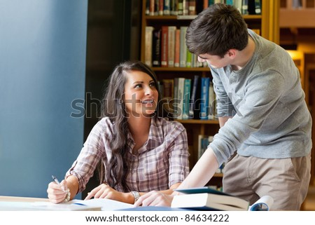 Young students helping each other doing an essay - stock photo