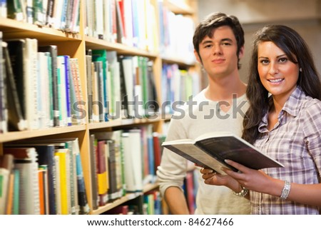 Young students holding a book in a library - stock photo