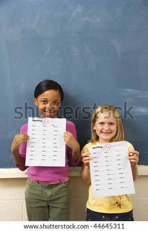 Young students holding spelling tests with good grades. Vertically framed shot. - stock photo