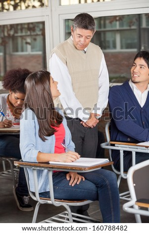 Young students looking at teacher while giving exam in classroom