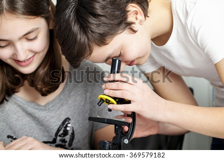 Young students looking through microscope
