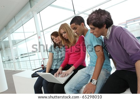 Young students sitting in front of a laptop computer - stock photo