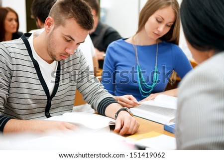 young students studying together in classroom - stock photo