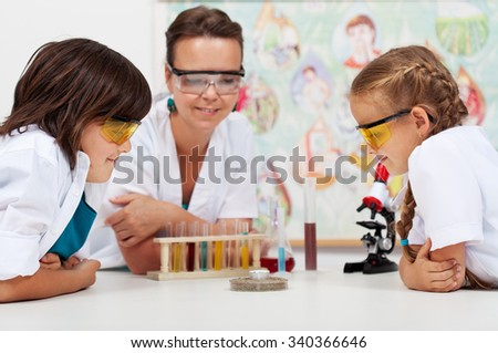 Young students watching an experiment in elementary science class - supervised by a teacher - stock photo
