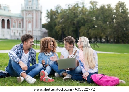 Young students with laptop outdoors - stock photo