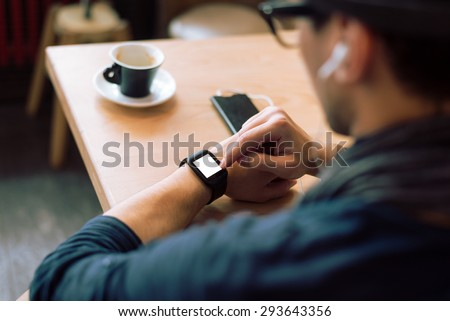 Young stylish and fashionable man checking his smartwatch in cafe bar. High angle shot. Selective focus. Toned image. - stock photo