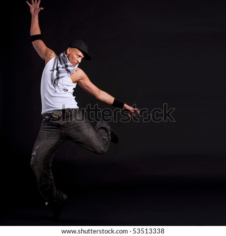 Young stylish asian dancer in front of black background moving to hip hop music. - stock photo