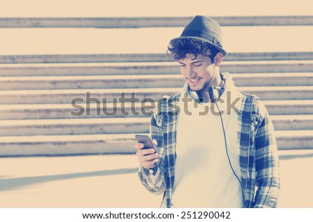 young stylish bearded man in Hoodie checkered shirt listening music in the city instagram style - stock photo