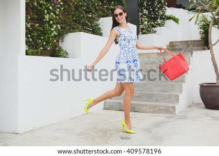 young stylish beautiful woman in blue printed dress, red bag, sunglasses, happy mood, fashion outfit, trendy apparel, smiling, summer, accessories, playful, walking, running on high heel yellow shoes - stock photo
