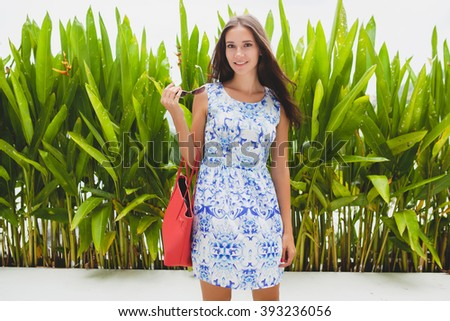 young stylish beautiful woman in blue printed dress, red bag, sunglasses, happy mood, fashionable outfit, trendy apparel, smiling, summer, accessories - stock photo