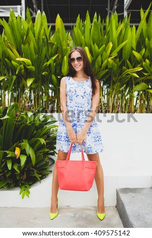 young stylish beautiful woman in blue printed dress, red bag, sunglasses, happy mood, fashionable outfit, trendy apparel, smiling, standing, summer, yellow high heel shoes, accessories - stock photo