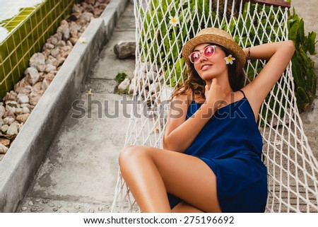 young stylish beautiful woman in pink sunglasses and straw hat blue dress lay in hammock at resort pool, smiling happy, enjoying summer day, vacation, relax, flower in hair - stock photo