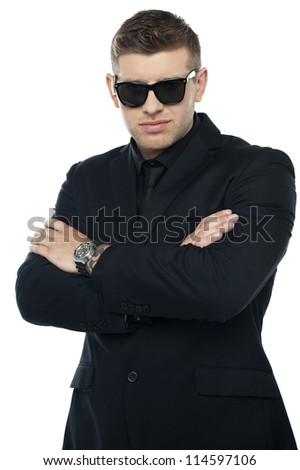 Young stylish bouncer in a black suit, arms folded. Half length portrait - stock photo