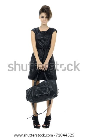 Young stylish brunette posing with black purse. Isolated over white - stock photo