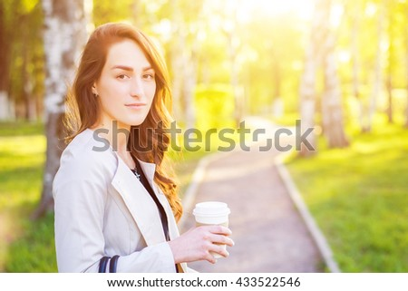 Young stylish business woman drinking coffee in a park at summer sunset. - stock photo