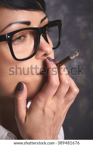 Young stylish business woman  in glasses smoking and thinking, creative process with cigarette, mouthfuls in art space with grey background - stock photo