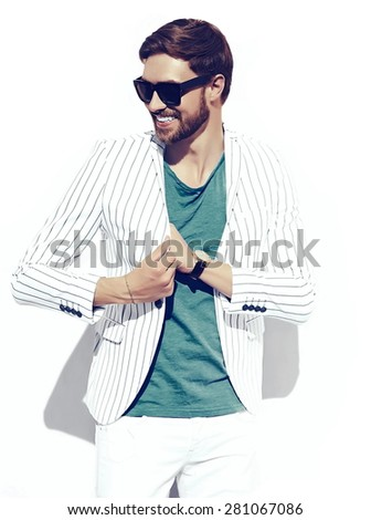 Young stylish confident happy handsome businessman model  in suit  lifestyle in the street standing near wall - stock photo