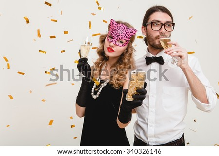 young stylish couple in love on white background holding glasses and drinking champagne, making self photo, celebrating new year, wearing black dress, mask, happy carnival disco party, having fun - stock photo