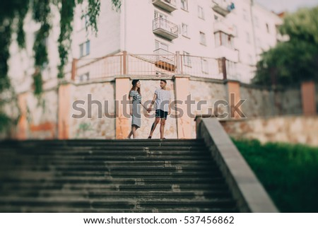 Young stylish couple on concrete stairs